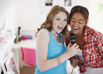 Teenage girls singing into microphone