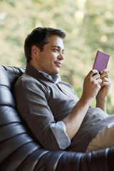 Man reclining in chair reading electronic book