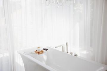White curtains and modern bathtub in bathroom