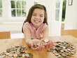 Smiling girl holding handful of coins