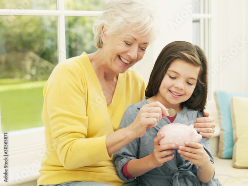 Grandmother putting coin into granddaughter?s piggy bank