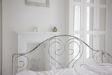 """Old-fashioned bed in elegant, white bedroom"""