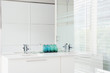 """""""Glass walls and sink in modern, white bathroom"""""""