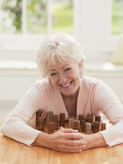 Smiling woman protecting stacks of coins