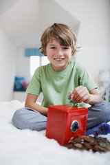 Boy putting coins into safe piggy bank
