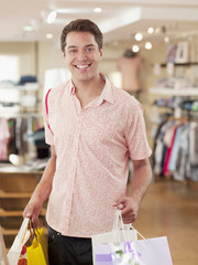 Man carrying shopping bags in clothing store