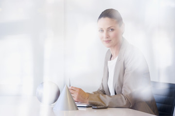 Businesswoman sitting at desk with sphere and cone