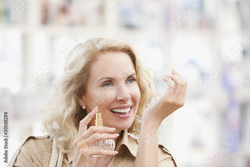 Smiling woman testing perfume in store