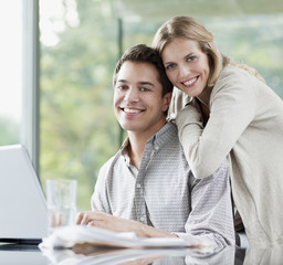 Smiling couple using laptop together