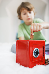 Boy putting coin into safe piggy bank