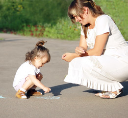 The child with mum draw a chalk on asphalt