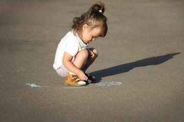The child drawing a chalk on asphalt