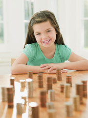 Smiling girl sitting with stacks of coins