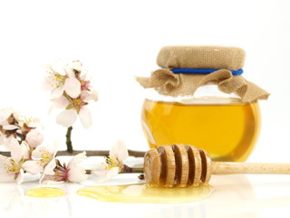 Honey in a jar, flowers and honey dipper