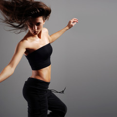 A young brunette dancer is caught in a beautiful jump
