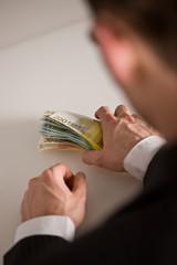 Mann greift Geldscheine
