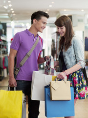 Smiling couple looking in shopping bag in store