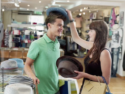 Smiling couple shopping for hats in store