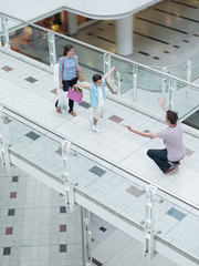 Son running towards father in shopping mall