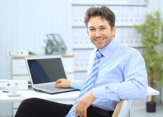 Businessman sitting at office desk working on laptop