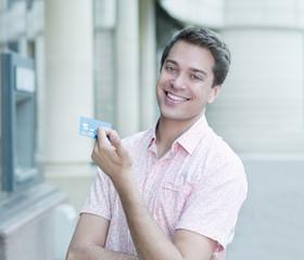 Smiling man holding credit card near ATM machine