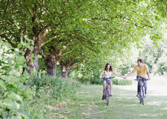 Couple holding hands and riding bicycles