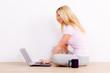 junge frau sitzt auf dem boden mit ihrem laptop