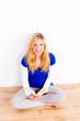 glückliche blondine sitz auf dem boden