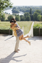 """""""Playful, happy couple hugging outdoors"""""""