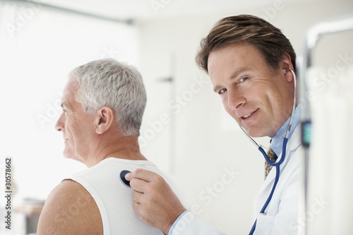 Doctor listening to man?s breathing in doctor?s office