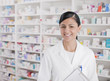 Smiling pharmacist standing in drug store
