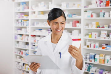 Pharmacist in drug store holding clipboard reading medication box