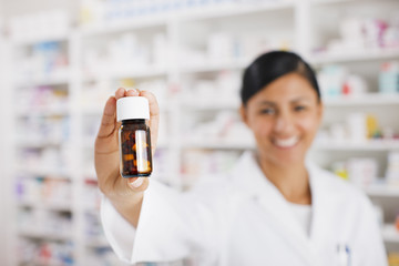 Pharmacist in drug store holding out pill bottle