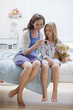 Mother checking daughter?s temperature with digital thermometer