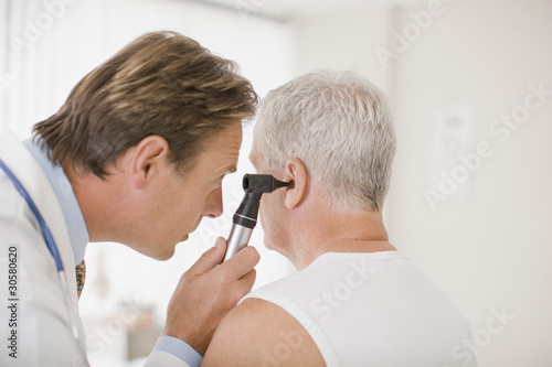 Doctor examining patient?s ear in doctor?s office