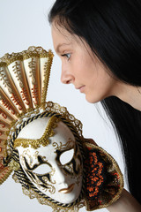 woman with long beauty hair holding Carnival Venetian mask