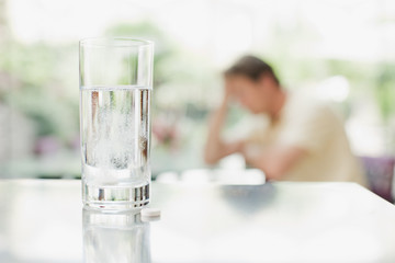 Glass of water and pill with unhappy man in background