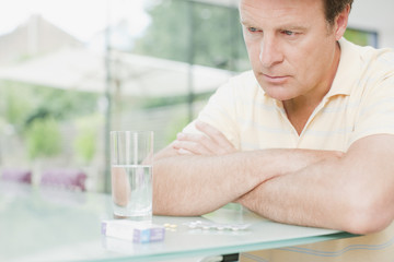 Man sitting with glass of water and box of pills