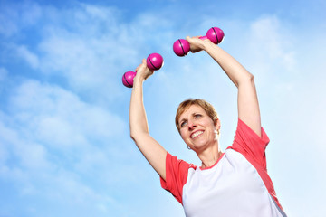 Mature woman exercising outdoors with bumbbells