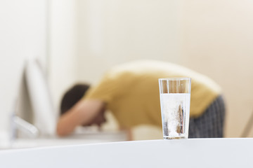 Glass of dissolving medicine with vomiting man in background