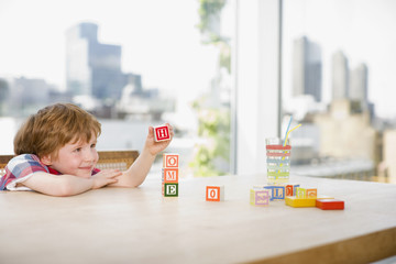 Boy stacking alphabet blocks that spell ?home?