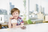 Boy putting cherry on ice cream sundae