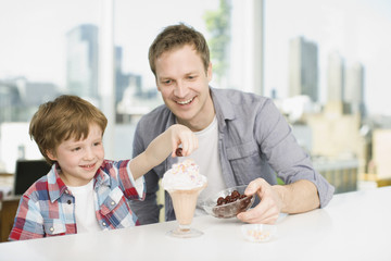 Father watching son put cherry on ice cream sundae