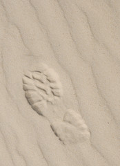 Sport footwear print on light sand with diagonal pattern
