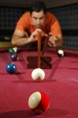 Person playing snooker (focus on the first ball)