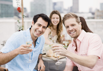 Laughing friends drinking Champagne at outdoor party