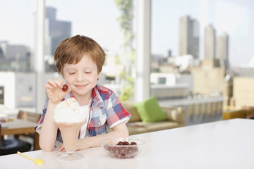 Smiling boy putting cherry on ice cream sundae