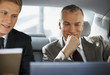 Businessmen working in back seat of car
