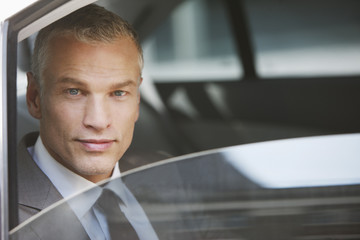 Businessman sitting in back seat of car