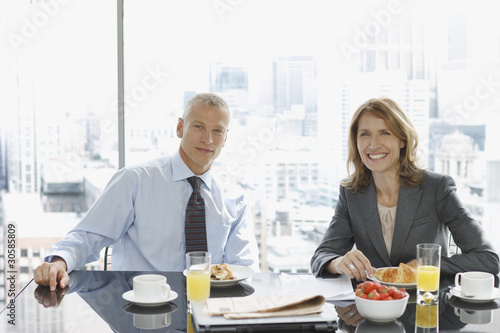 Smiling business people having breakfast